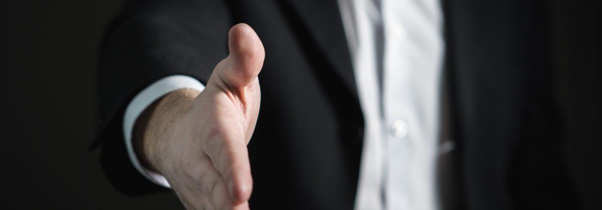 man in pak steekd hand uit vanwegedevaststellingsovereenkomst